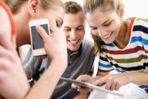 Three young adult friends looking at digital tablet