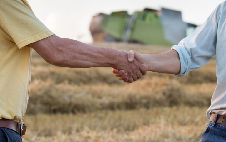 Two farmers shaking hands in field - Agribusiness Recruiting - Agricultural Appointments